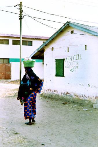 Frau mit Last auf dem Kopf von hinten auf der Straße.