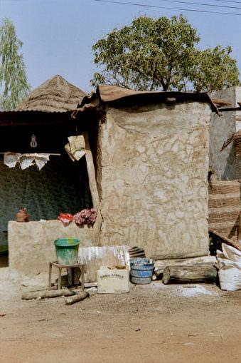 Kiste mit Mama Afrika Aufschrift vor Hütte.