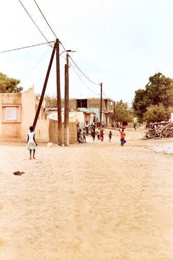 Menschen in der Ferne auf einer Sandstraße mit Telegrafenmasten.