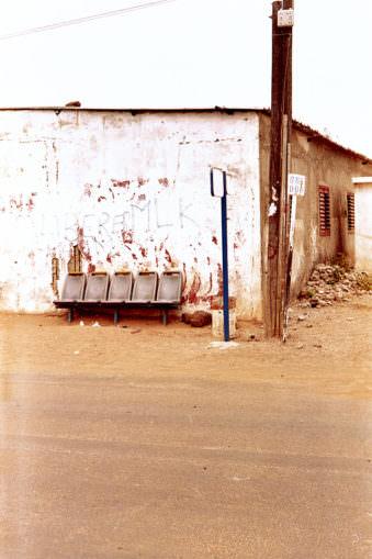Bushaltestelle an einer ramponierten Hauswand mit 4 Sitzplätzen.
