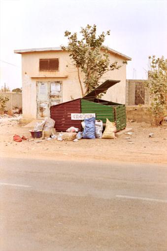 Müllcontainer mit Müllsäcken am Straßenrand.
