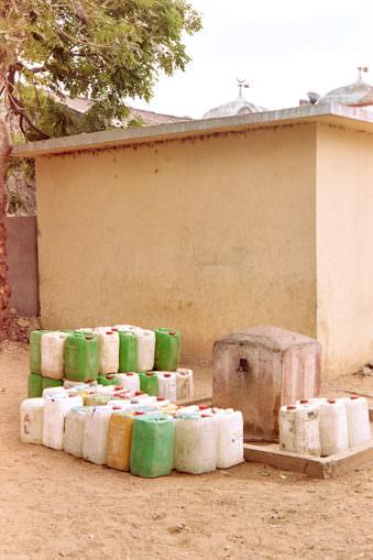 Wasserkanister vor einer Hauswand an einer Wasserstelle.