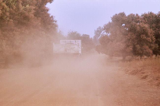Staubwolke aufgewirbelt von einem Laster auf Sandpiste.