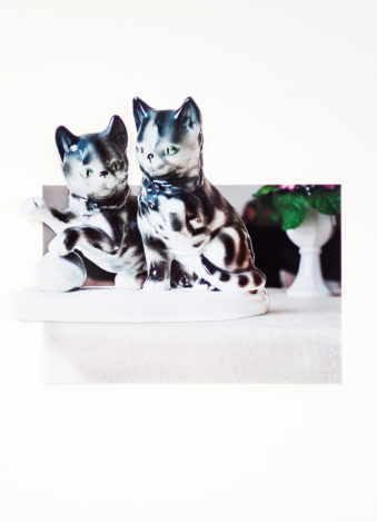 Zwei Porzellankätzchen vor einem Hintergrund.