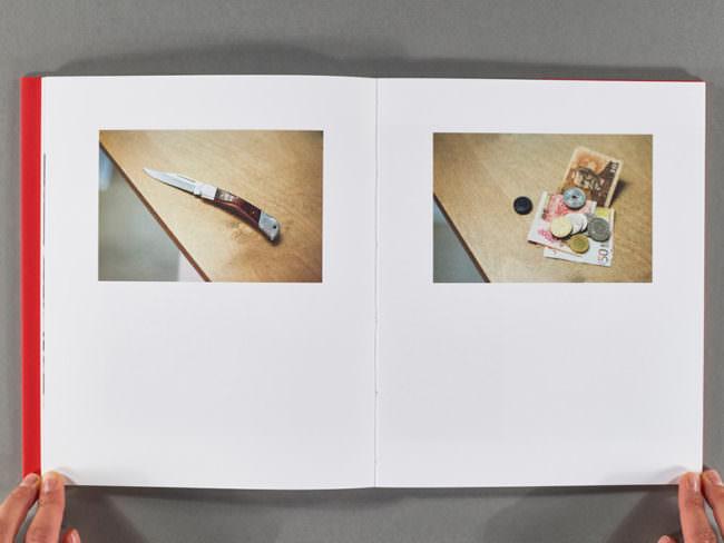 Aufgeschlagenes Buch mit 2 Fotografien aufgehalten von 2 Händen.