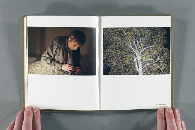 Aufgeschlagenes Buch mit zwei Fotografien, aufgehalten von zwei Händen.