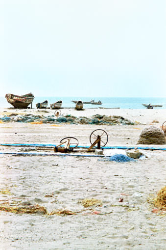 Strandblick mit Horizont an dem Boote liegen und Fischernetzspulen aufgebaut sind.