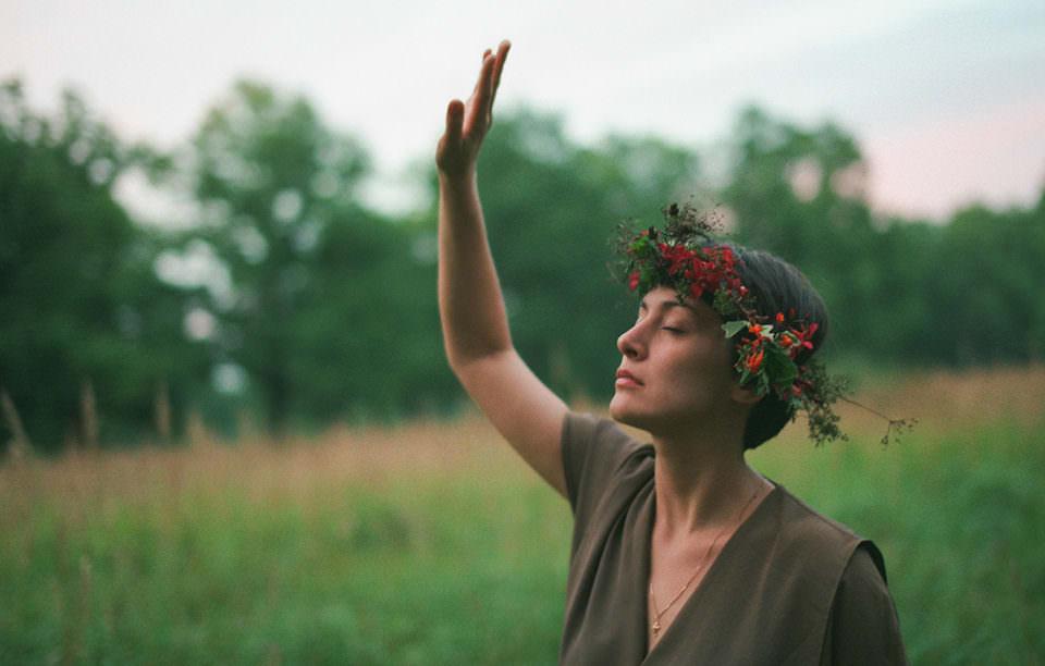 Eine Frau mit Blumenkranz im Haar hebt einen Arm.