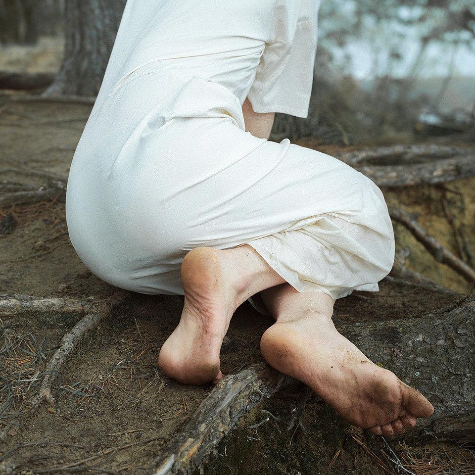 Eine Frau mit nackten Füßen und weißem Kleid sitzt auf dem dreckigen Boden.