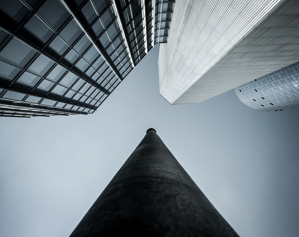 Blick von unten zu mehreren Hochhäusern und dem Himmel darüber hinauf.