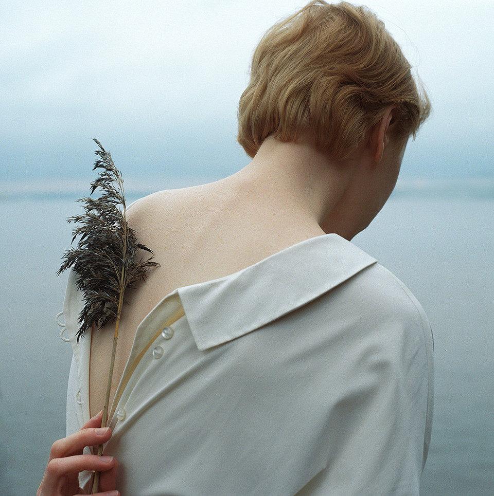 Eine Frau hält sich einen Farnwedel vor den Rücken.