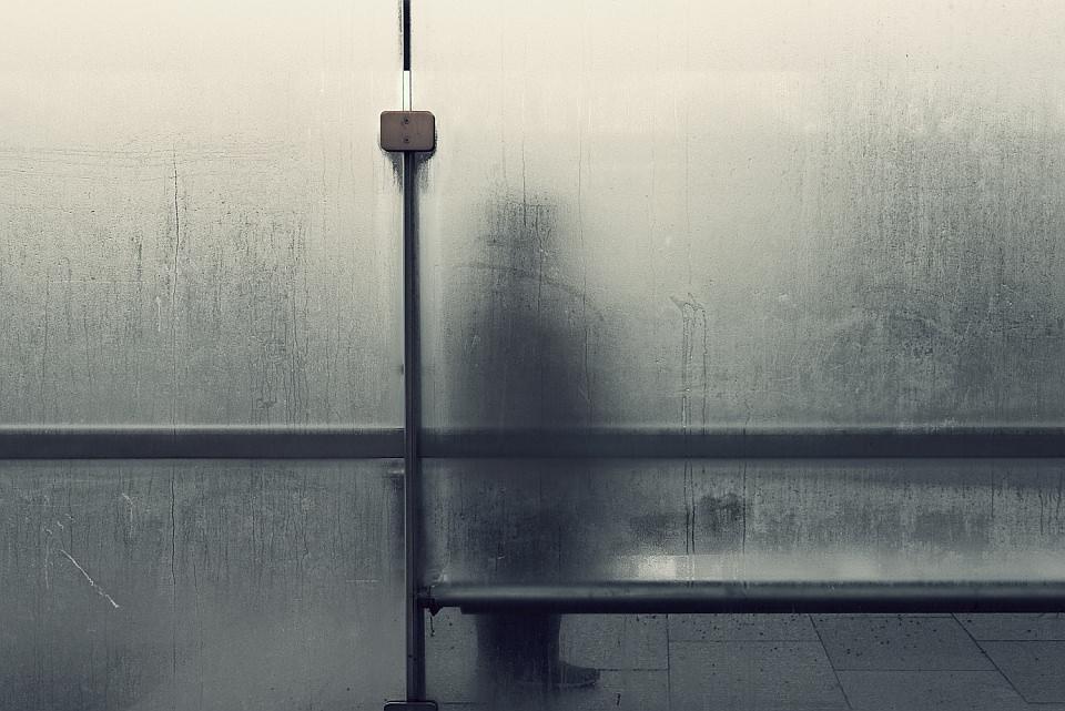 Beschlagene Scheibe an einer Bushaltestelle, dahinter der Schemen eines Menschen.