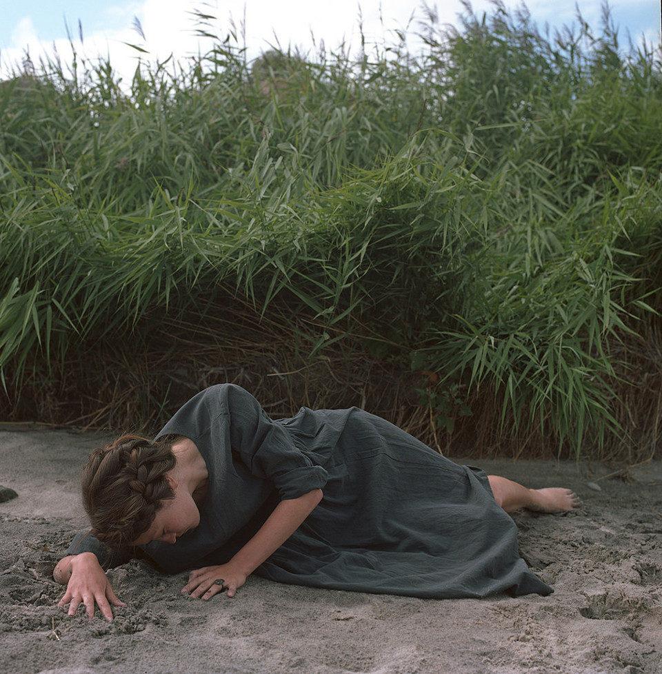 Eine junge Frau mit Zöpfen liegt auf dem Strand.