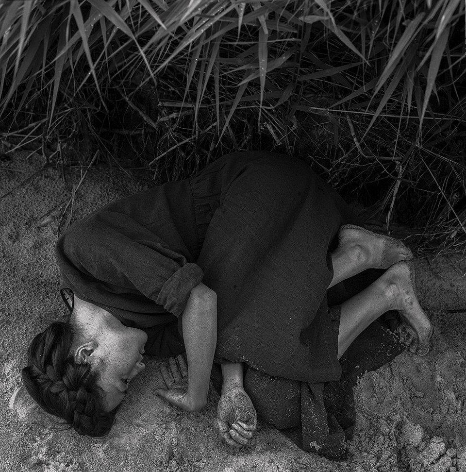 Eine junge Frau mit Zöpfen liegt auf dem Strand eingekringelt.