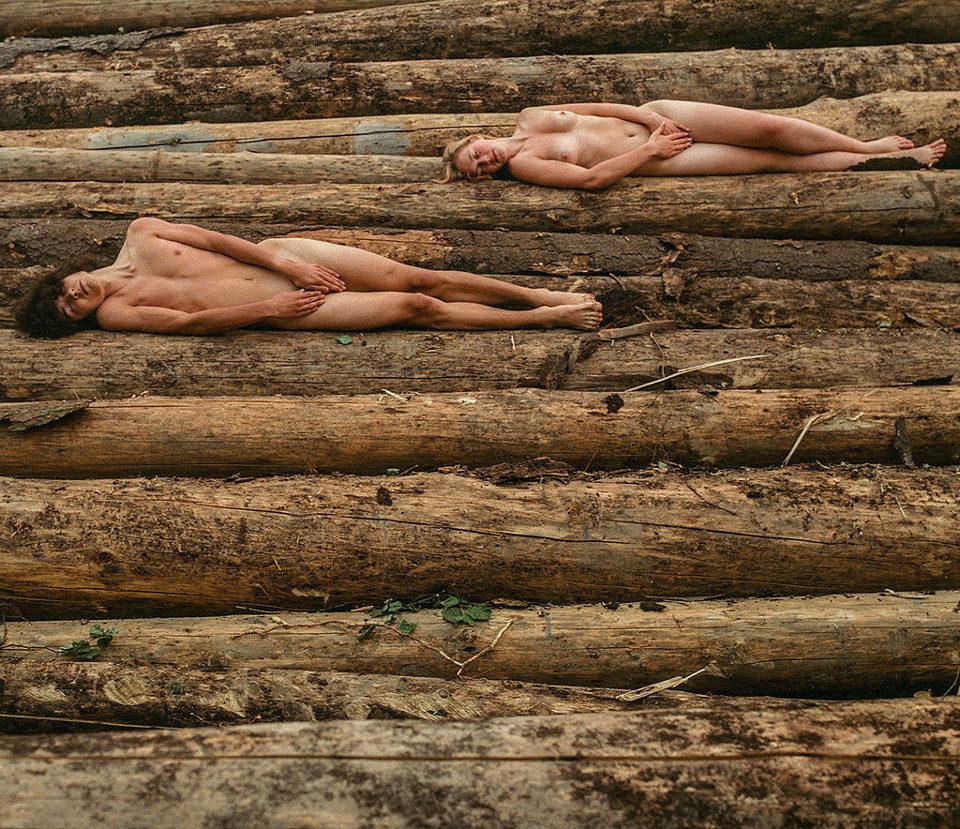 Zwei nackte Menschen liegen auf gestapeltem Holz.