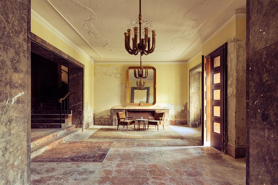 Blick in einen verlassenen, aber herrschaftlich eingerichteten Raum in warmen Farben.