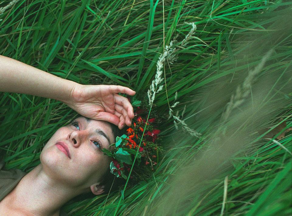 Eine Frau mit Blumenkranz im Haar liegt in einer Wiese.