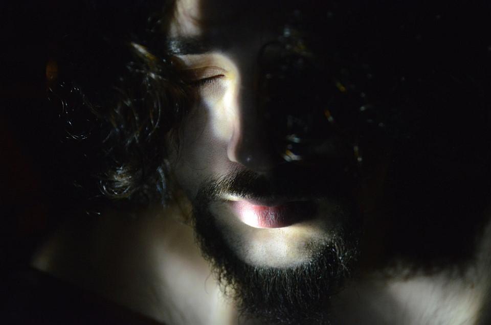 Männerportrait, beleuchtet nur durch einen schmalen Lichtstreif quer übers Gesicht.
