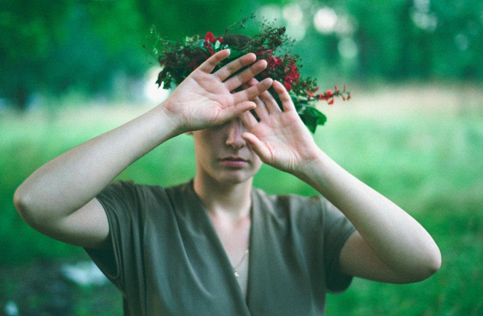 Eine Frau mit Blumenkranz im Haare hält sich die Augen zu.