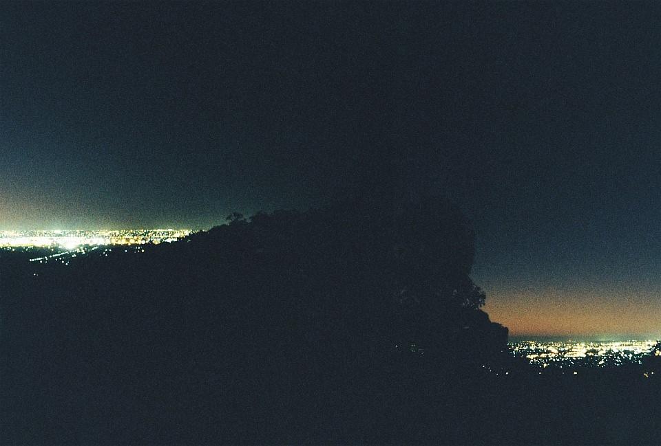 Lichter zweier Städte, nachts links und rechts eines Berges gelegen.