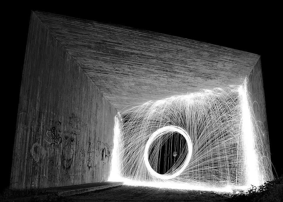 Funkensprühender Kreis in einer Unterführung, schwarzweiß.