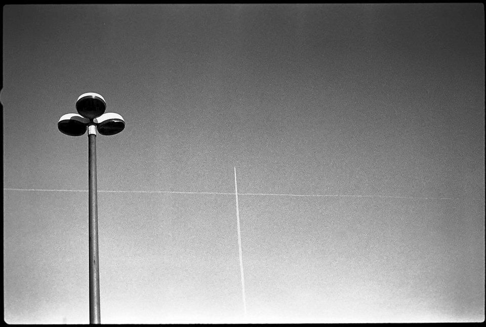 Zwei sich am Himmel kreuzende Kondensstreifen, davor eine Straßenlaterne.