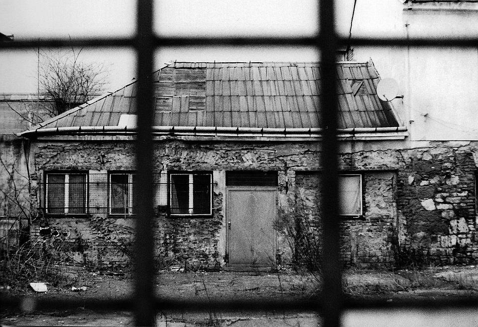 Schwarzweiß, Blick aus einem Fenster zu einem alten Haus.