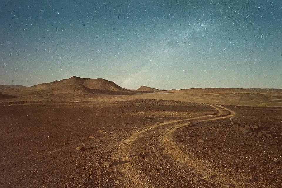 Schotterpiste in einer kargen Landschaft, die auf einen Hügel zuführt, hinter dem ein Sternenhimmel mit Milchstraße zu sehen ist.