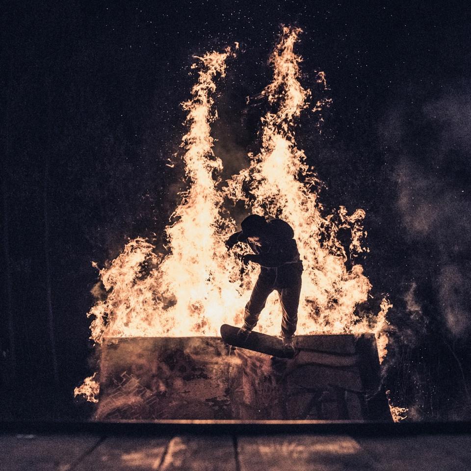 Ein Skateboarder bei der Fahrt über eine brennende Rampe.