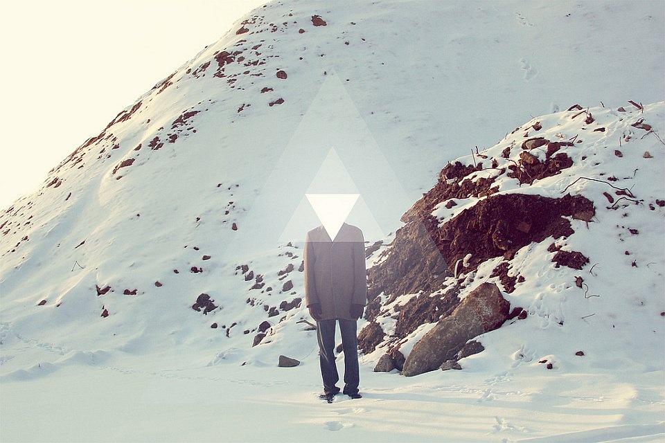 Ein Mann steht vor einem schneebedeckten Hang, statt einem Kopf hat er ein leuchtendes Dreieck.