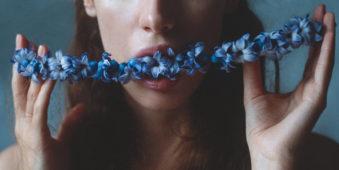 Eine Frau hat einen blaue Blumengirlande im Mund.