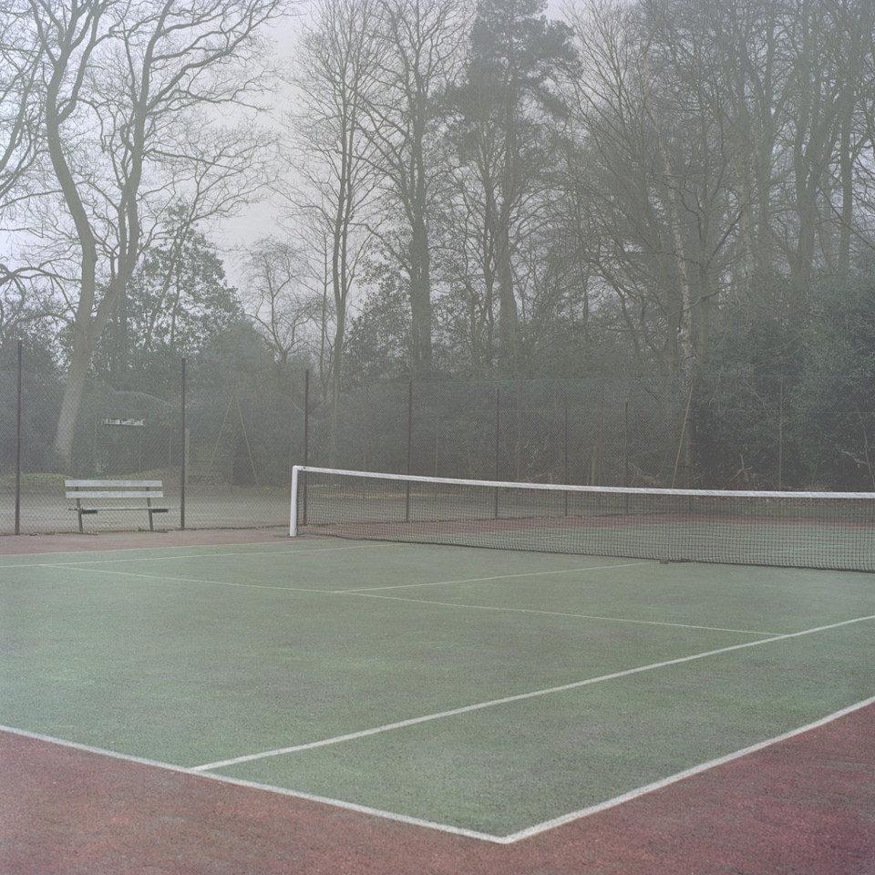 Ein leeres Tennisfeld liegt im Nebel.