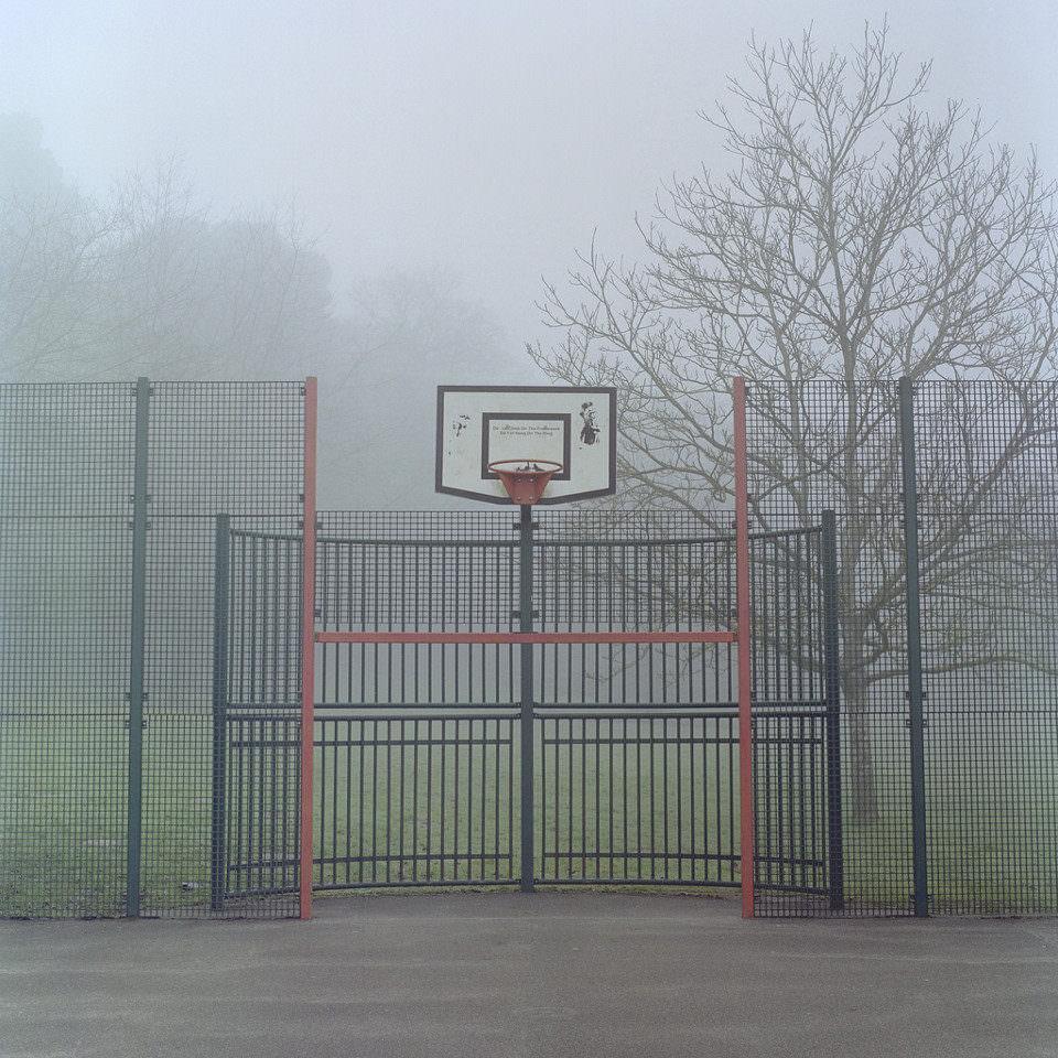 Ein leeres Basketballfeld mit Korb liegt im Nebel.