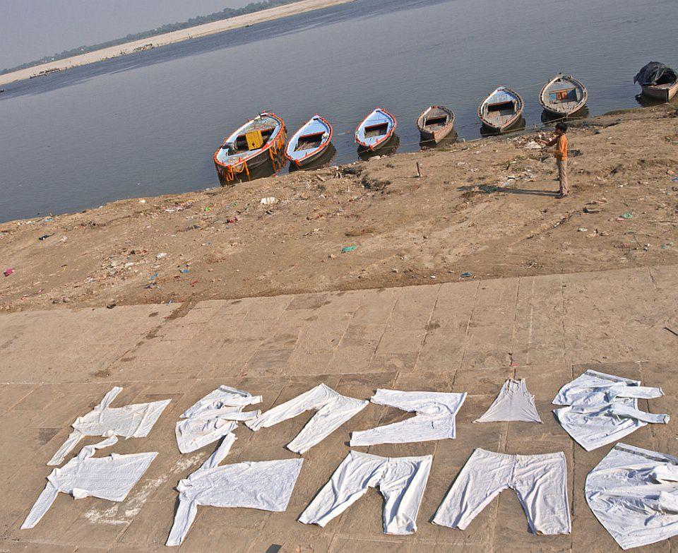 An einem Ufer mit mehreren Booten liegen weiße Wäschestücke zum Trocknen aus.
