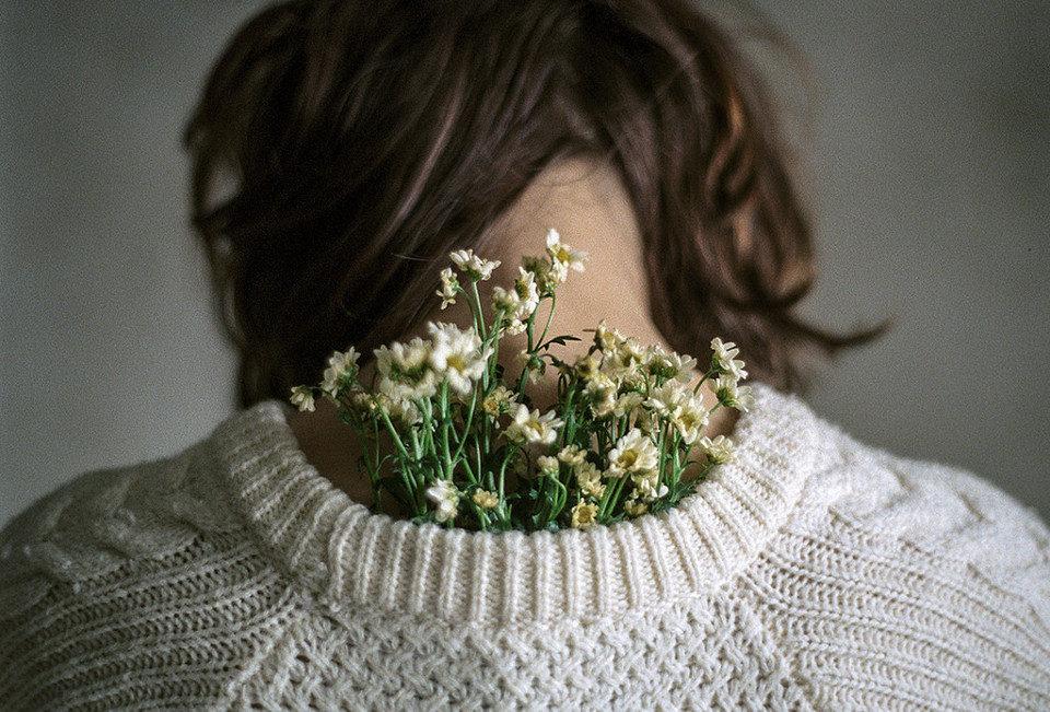 Eine Frau hat einen Blumenstrauß im Pulloverausschnitt.