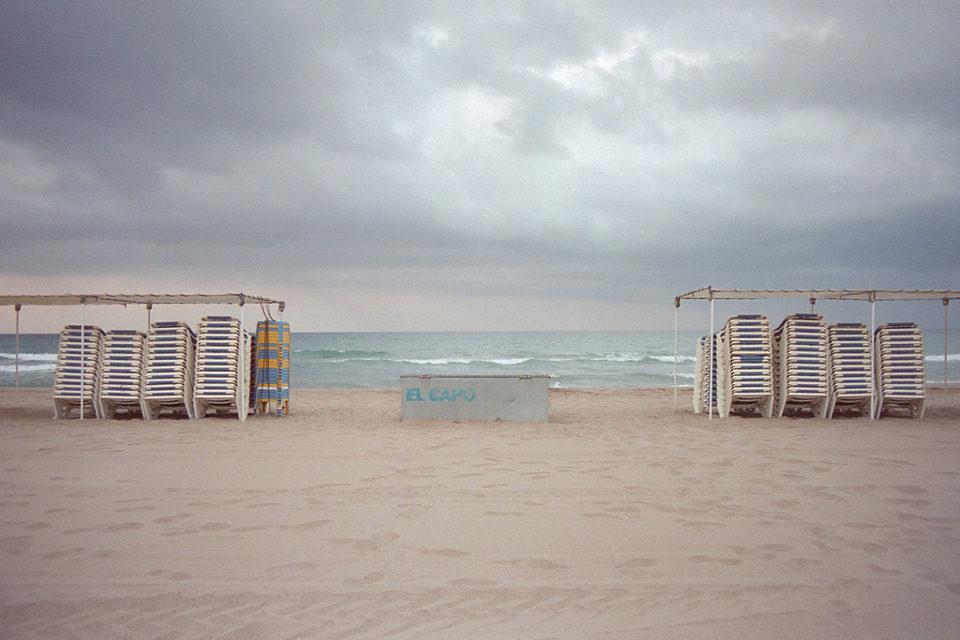 Badeliegen sind an einem leeren Strand gestapelt.