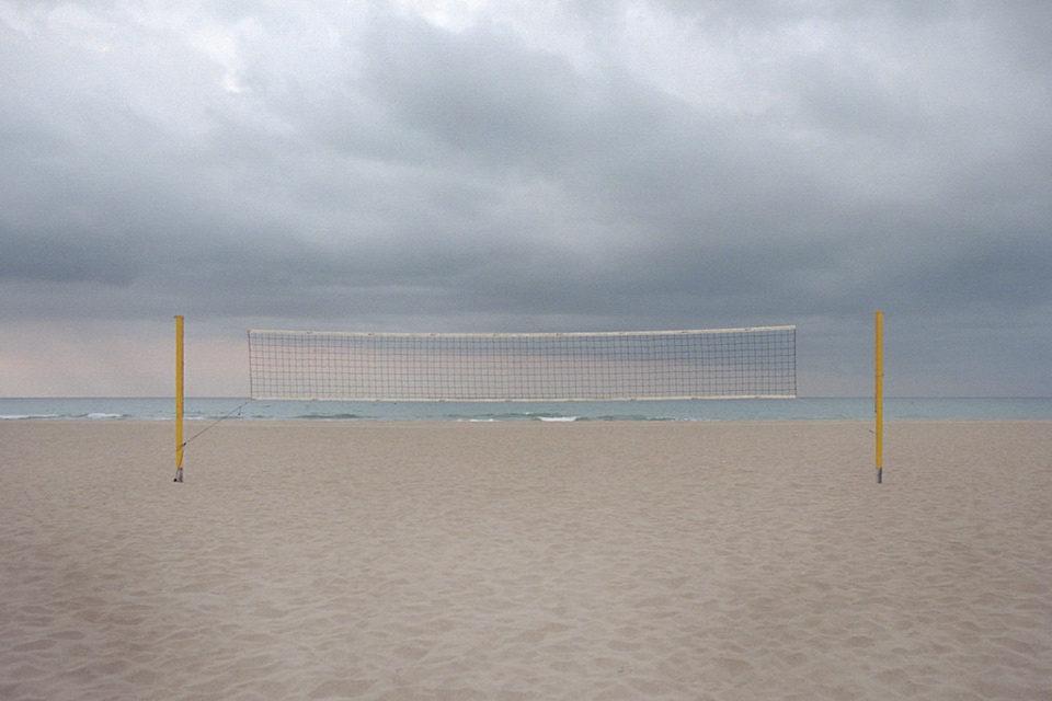 Ein Volleyballnetz steht an einem leeren Strand.