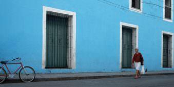Eine Frau geht vor einer blauen Hausfassade entlang, an der auch ein Fahrrad lehnt.