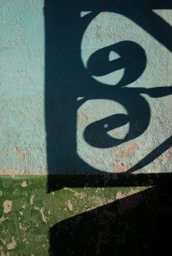 Schatten eines gusseisernen Zauns auf abblätternder Hausfarbe.