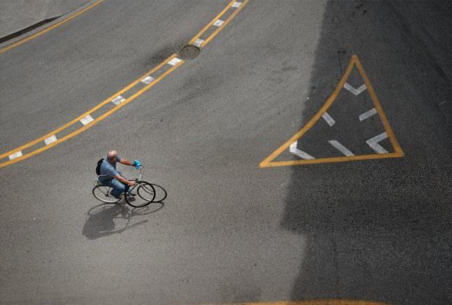 Aufnahme von erhöhter Position eines Fahrradfahrers auf einer Straße mit weißen und gelben Markierungen.