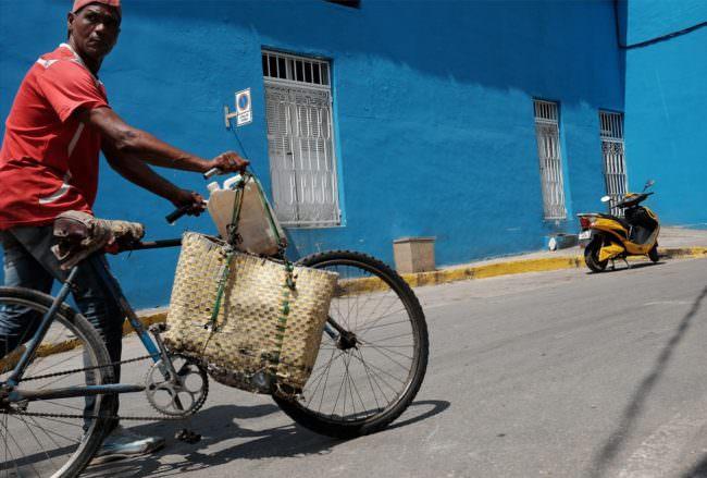 Ein Mann schiebt ein Fahrrad vor einer blauen Hauswand, im Hintergrund ein Motorrad.
