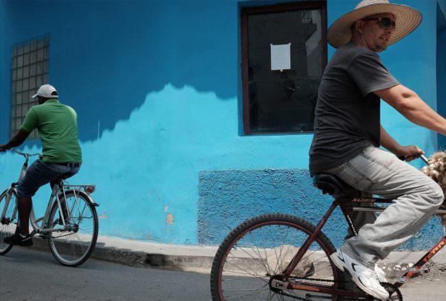 Zwei Männer fahren auf Fahrrädern vor einer blauen Hausfassade in entgegengesetzter Richtung.