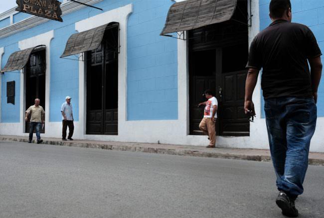 Vier Männer stehen verstreut vor einer blauen Hausfassade.