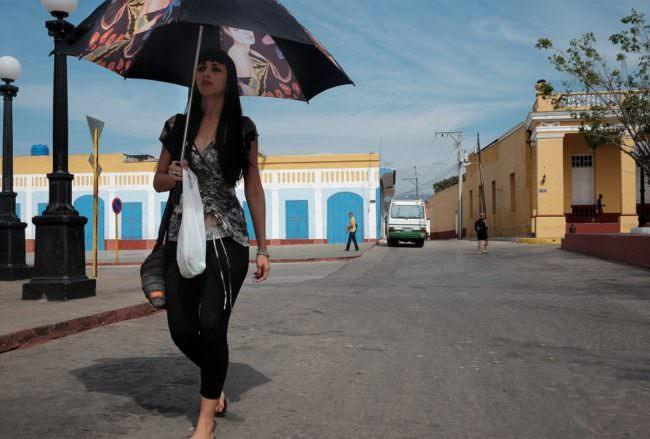 Eine Frau mit Sonnenschirm geht auf einer breiten, leeren Straße.