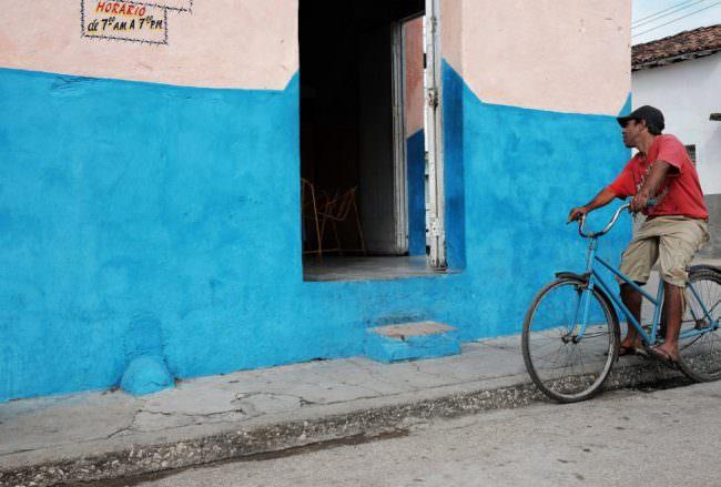 Ein Mann auf einem Fahrrad schaut durch die geöffnete Tür in ein Geschäft.