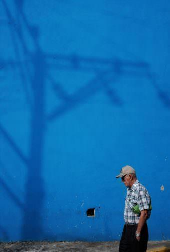 Mann vor einer blauen Hauswand, auf die ein Strommast seinen Schatten wirft.