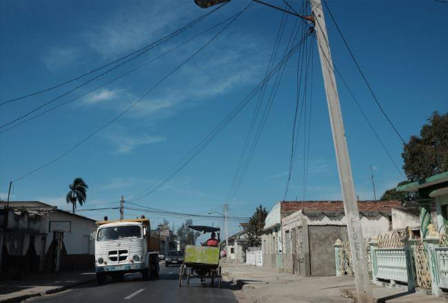 Blick in eine kubanische Straße mit großem Strommast im Vordergrund.