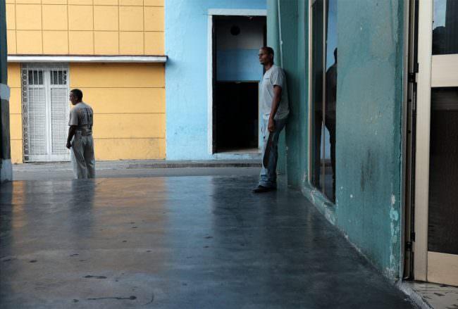 Durchgang, in dem gelbe und blaue Fassaden und zwei Männer zu sehen sind.