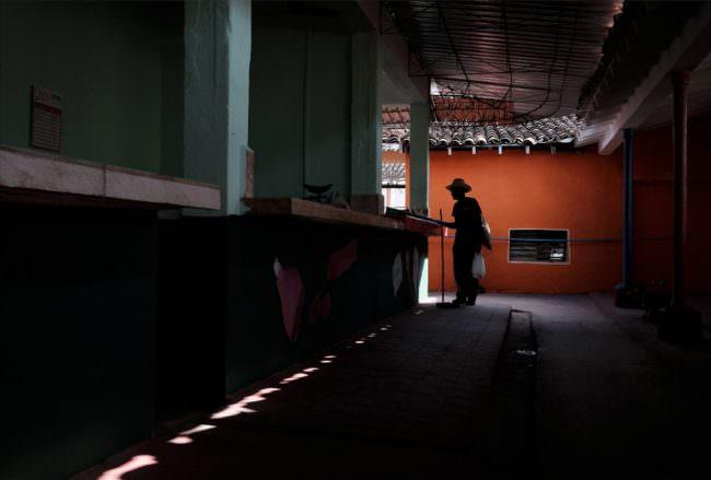 Dunkler Durchgang, in dem die Silhouette eines Mannes vor einer orangen Fassade zu sehen ist.