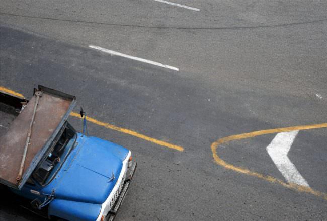 Blauer Transporter auf einer Straße, Perspektive von oben.